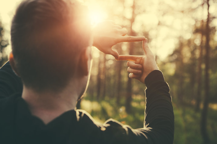 Human hands framing distant sun rays on outdoor